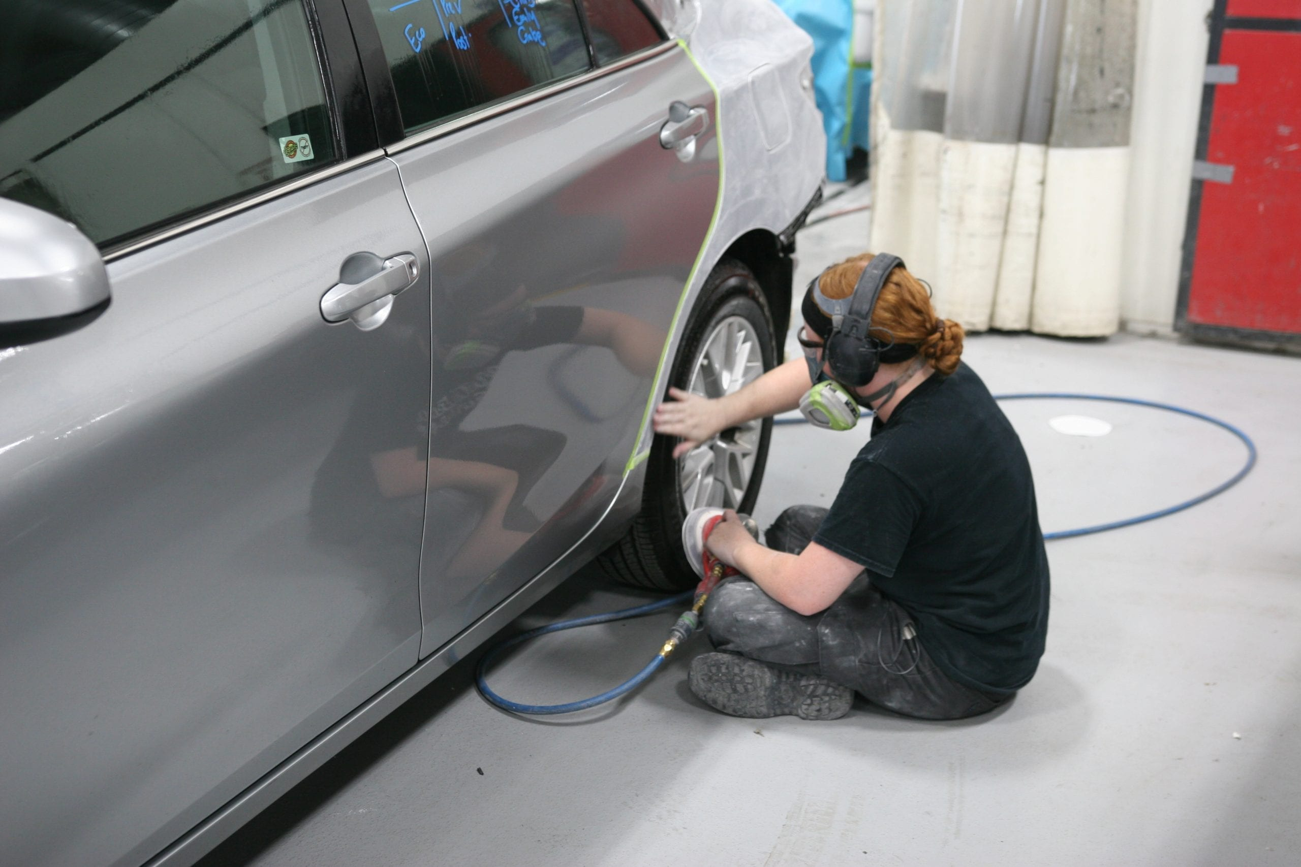 Collision technician working on car