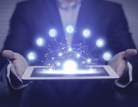 man holding tablet with digital marketing symbols